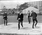 Beatles - Beatles Group Picture Playing and Dancing on the White Concrete Floor in Black Suit and Vest