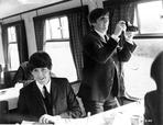 Beatles - Beatles Paul McCartney Hand on the Table and Ringo Starr standing Holding a Camera