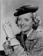 Bette Davis - Bette Davis Portrait smiling in Black Flat Hat in Checkered Suit and White Collar Shirt with Tie