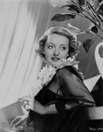 Bette Davis - Bette Davis Portrait Lying Back on a Table in Sunflower Garland and Black Linen Lace Long Sleeves