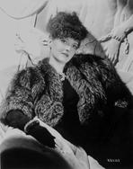 Bette Davis - Bette Davis Posed with Hand on the Lap in Black Fur Coat and Black Dress with Black Gloves