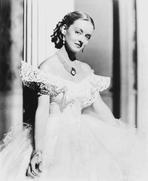 Bette Davis - Bette Davis Posed in White Lace Top Silk Gown and Necklace with Pearl Earrings
