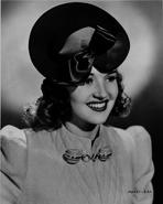 Betty Grable - Betty Grable Portrait in Black Hat and White Pointed Sleeve Cotton Dress with Brooch