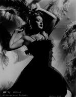 Betty Grable - Betty Grable Posed with Arms Raised Up in Black Strap Ruffled Sheer Top Velvet Dress on White Background