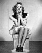 Betty Grable - Betty Grable Seated on a Box with Hands on the Chin in Black Pointed Short Sleeve Dress with White Fur on the Edge