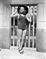 Betty Grable - Betty Grable Posed with Hands on the Hat in Black Round Hat and One Piece Swimsuit with Black Flats