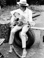 Bob Dylan - Bob Dylan Seated on Wheel Playing Guitar wearing White Long Sleeves and Slippers