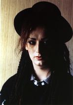 Boy George - Boy George Woman's wearing Black Dress and Black Hat Portrait