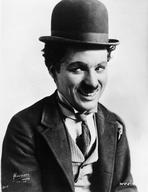 Charlie Chaplin - Charlie Chaplin smiling in a Coat and Tie