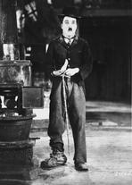 Charlie Chaplin - Charlie Chaplin standing in Black Suit while Holding a Chain