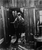 Charlie Chaplin - Charlie Chaplin standing in Black Suit with Dog