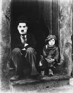 Charlie Chaplin - Charlie Chaplin Siting Beside Child in Black Tuxedo with Hat
