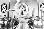 Charlie Chaplin - Charlie Chaplin standing in Nazi Uniform while One hand Raise with Cast Members