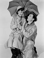 Gene Kelly - Gene Kelly Kneeling Down in Rain Coat