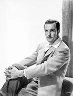 Gene Kelly - Gene Kelly Seated in Coat