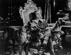 Greta Garbo - Greta Garbo sitting on a Chair with a Dog
