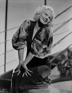 Jean Harlow - Jean Harlow Posed and Knelt on the Couch in Black Deep V-Neck Velvet Dress and Cotton Pleated Broad Sleeves with Hands on the Knees
