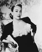 Joan Crawford - Joan Crawford Leaning on a Char wearing a Blouse