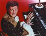 Liberace - Liberace with Man Playing Piano in Red Background