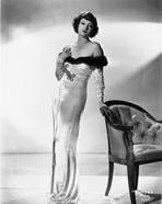 Myrna Loy - Myrna Loy standing in Off Shoulder Dress