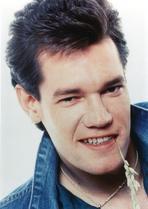Randy Travis - Randy Travis smiling in Close Up Portrait wearing Blue Denim Jacket