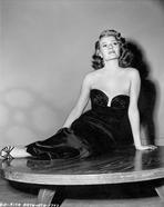 Rita Hayworth - Rita Hayworth Seated on Table in a Black Gown