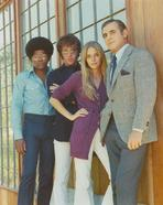 The Mod Squad - Mod Squad Posed in Group Picture Beside a Glass Window