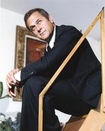 Tony Curtis - Tony Curtis Seated on the Stairs wearing Black Coat and Tie